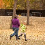 woman and girl at a trot in autumn leaves in a park