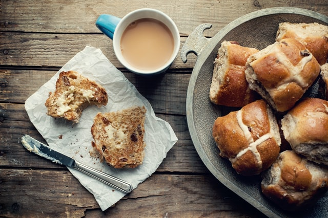 mug of tea and plate of hot cross buns with one split and buttered
