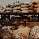 variety of artisan loaves and a wooden shelf