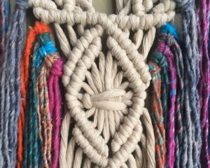 macrame piece with pink, blue and beige string