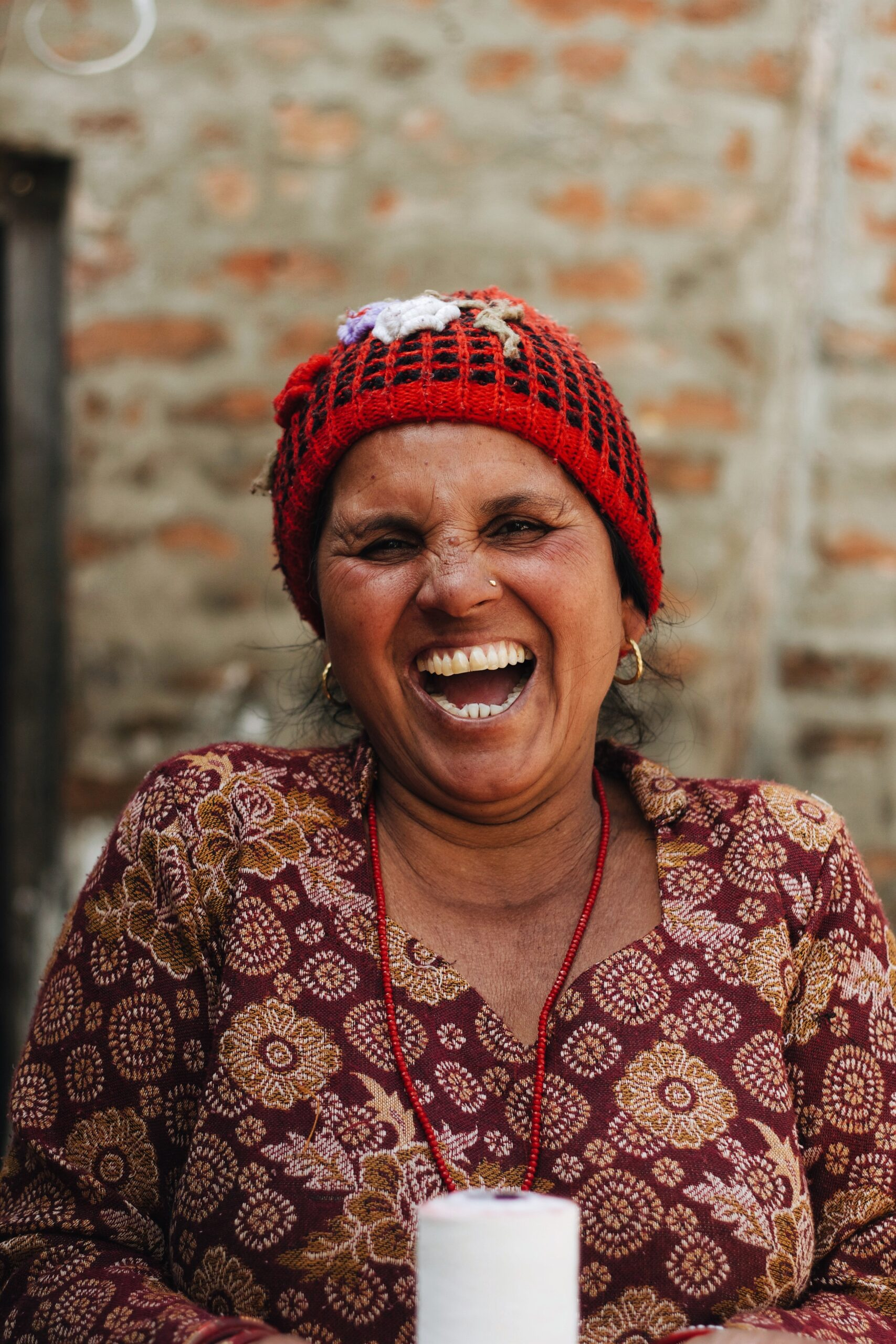 woman in knitted hat and colourful blouse laughing