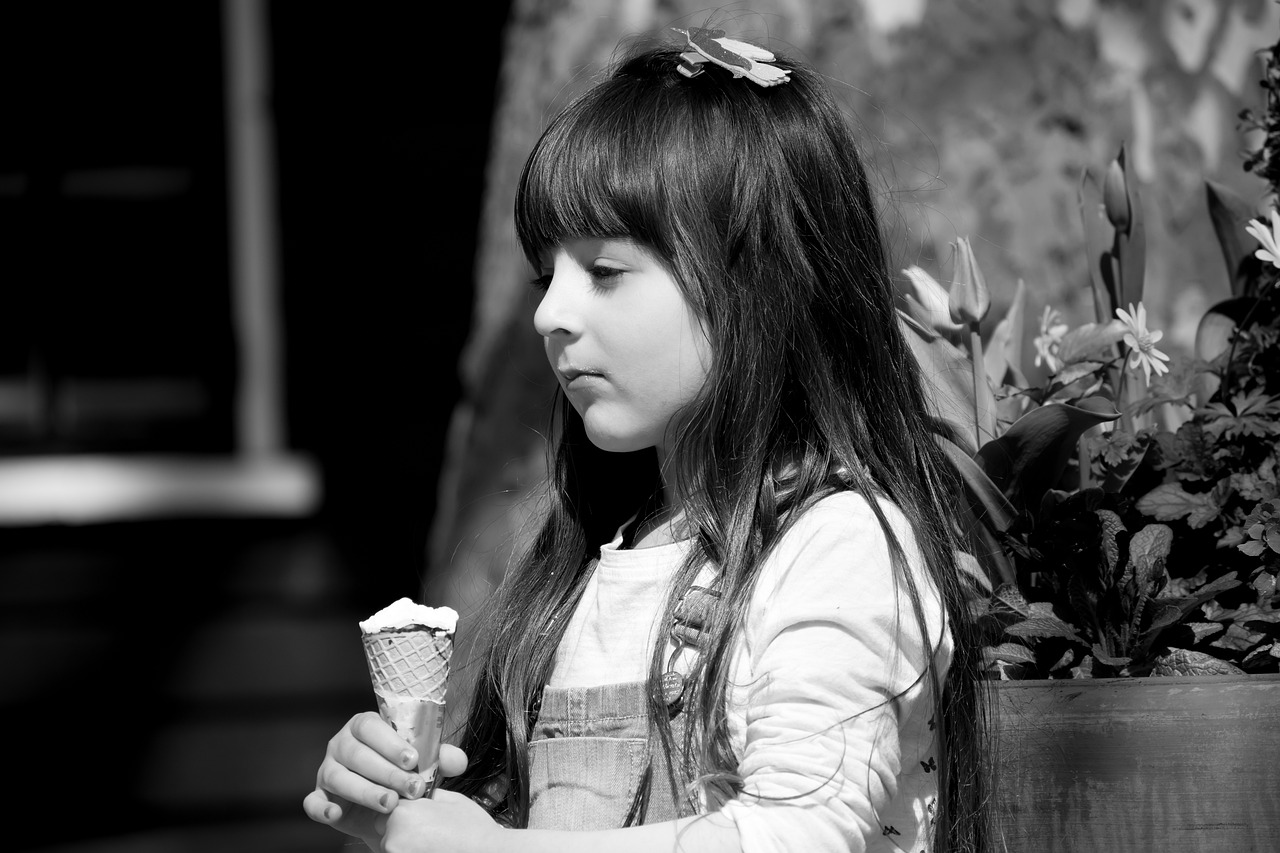 black and white photo of pensive child with ice cream