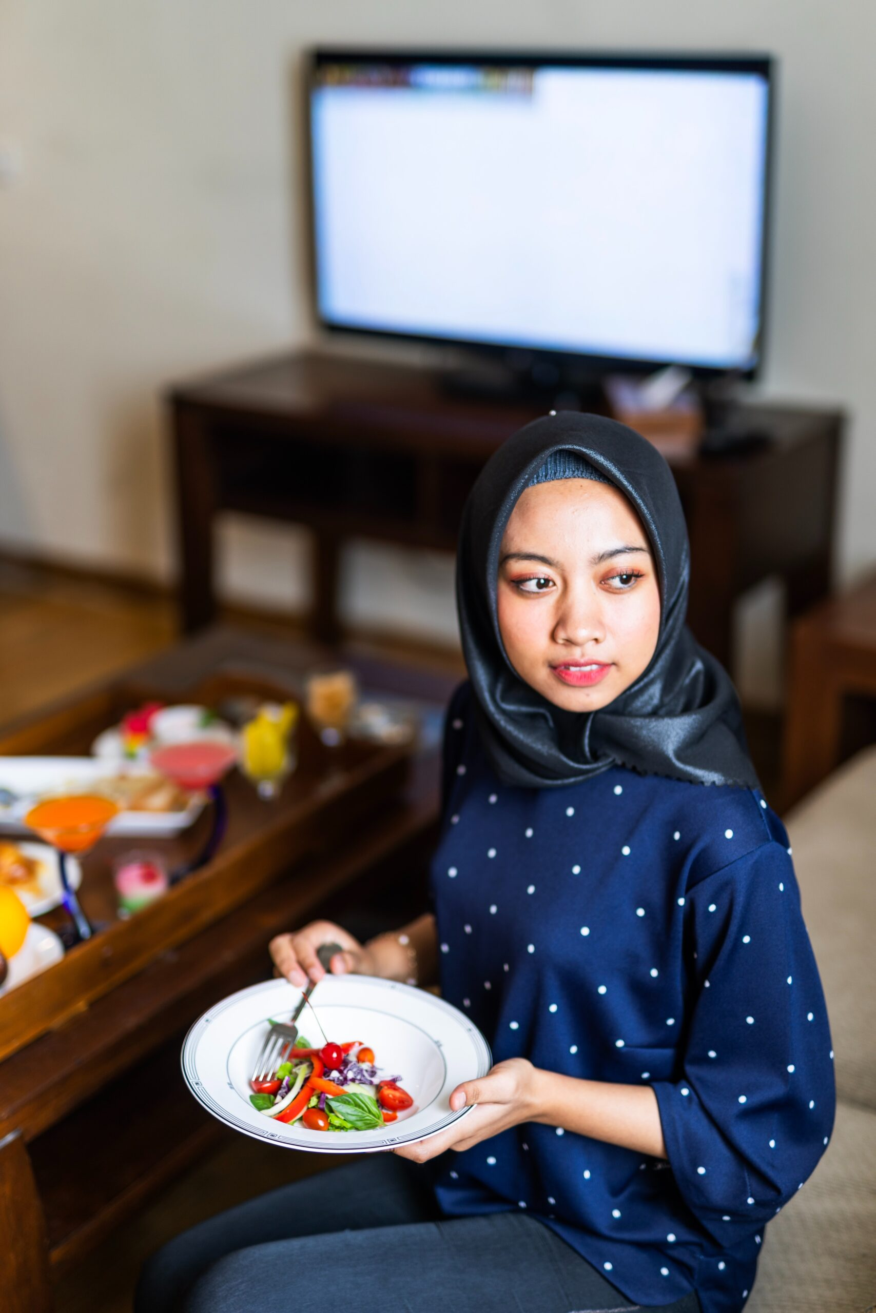 woman wearing hijab eating with tv on