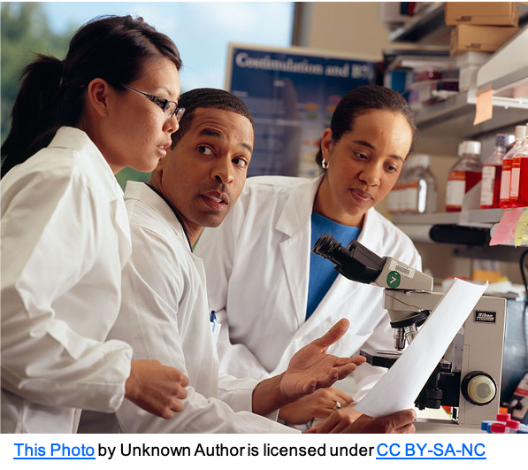 three adults in white coats in a lab