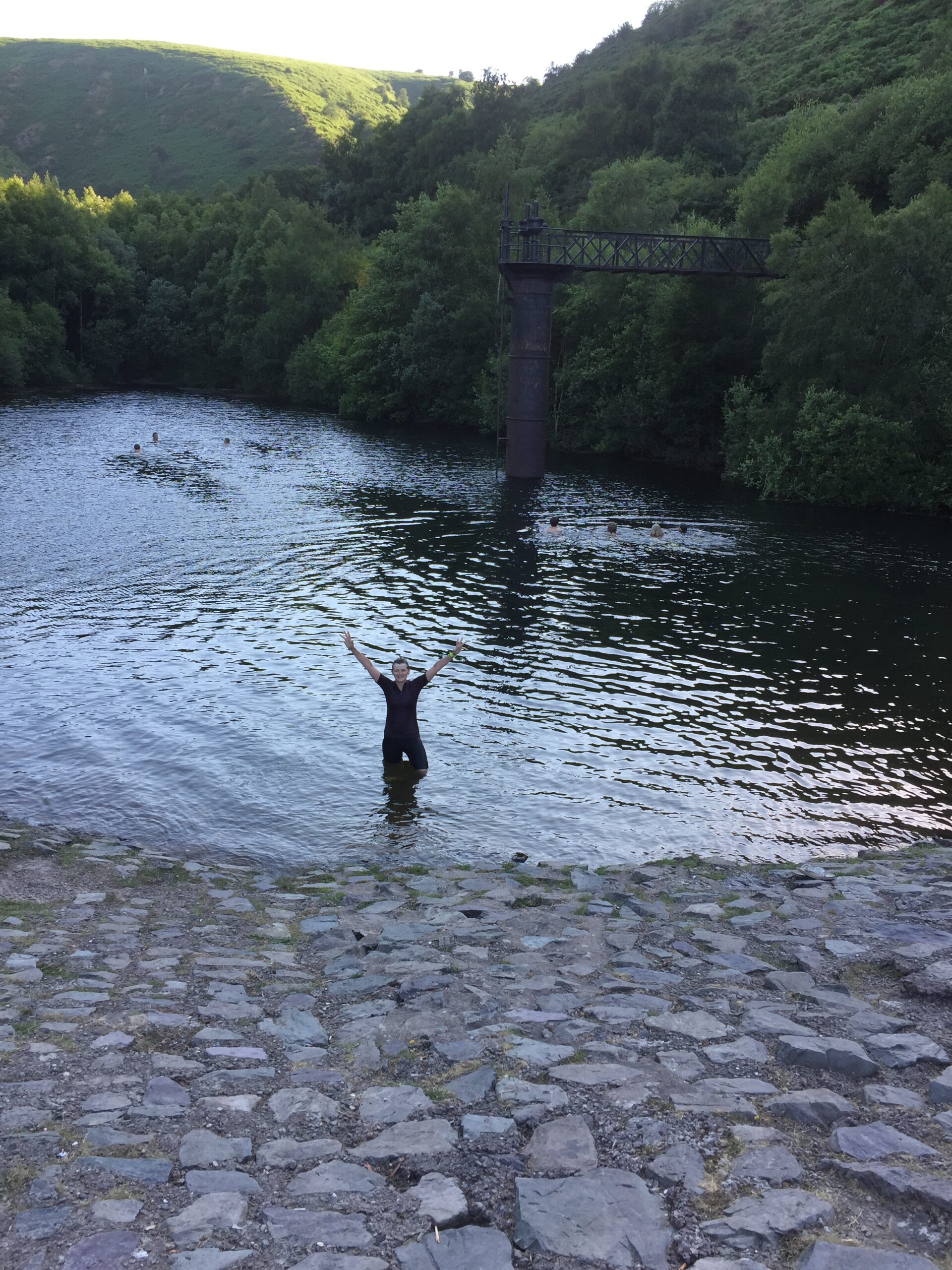 person emerging from swimming in old quarry, arms raised