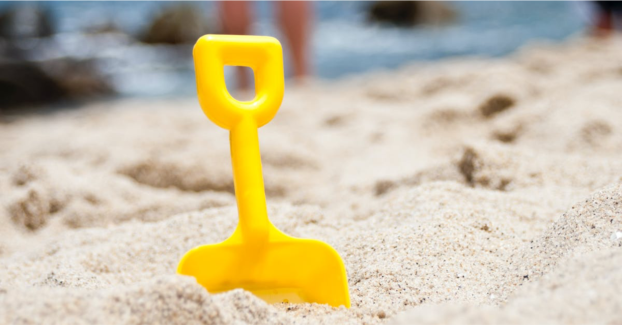 child's yellow plastic spade in sand