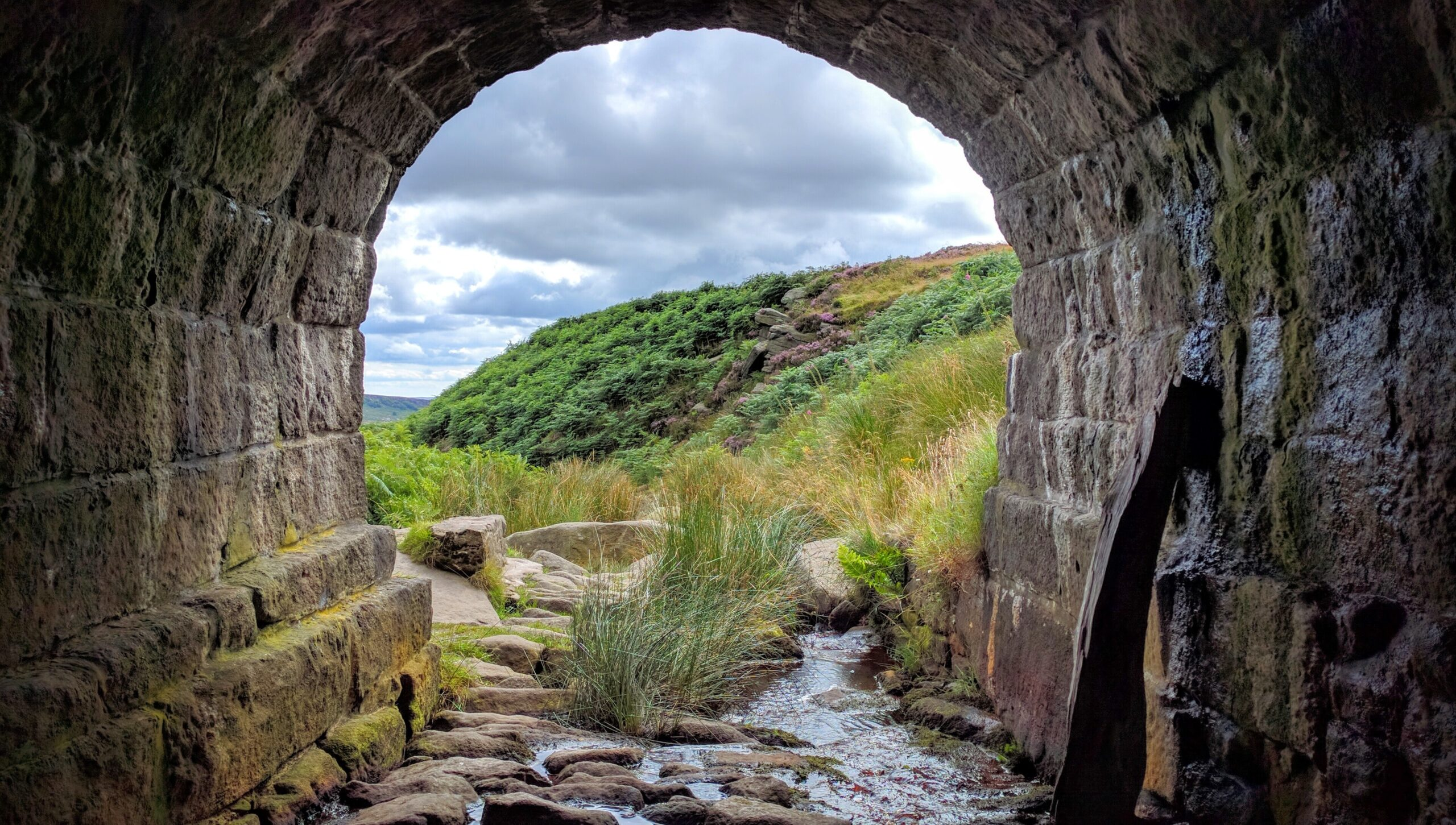 view onto fields and blue sky from arch under bridge, Hathersage